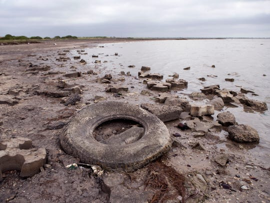 Trash, including this tire, litters the beach near