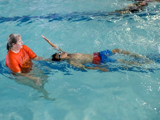 Annette DuVall (left) works with Joaquin Serrano,10,  as he swims on Thursday, May 3, 2018 at the Corpus Christi Natatorium.