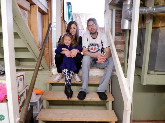 Matt, Brooke and Brinley Sorenson sit on the basement