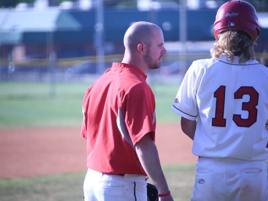Rossview coach Parker Holman talks with Jackson Carter (13) before an at-bat during their district baseball tournament game against Northwest Monday.