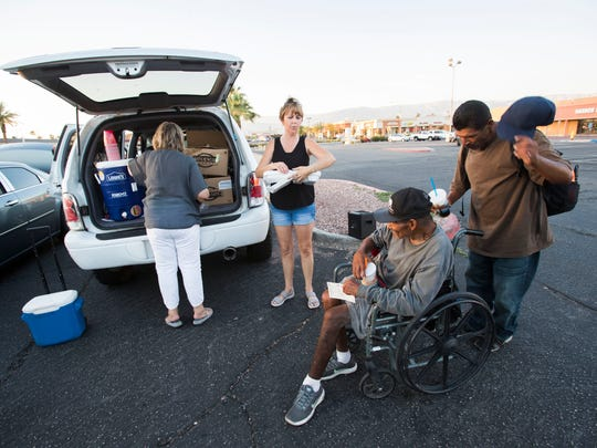 Homeless men are fed at a shopping mall parking lot by the Street Life Project in Indio on May 8, 2018.