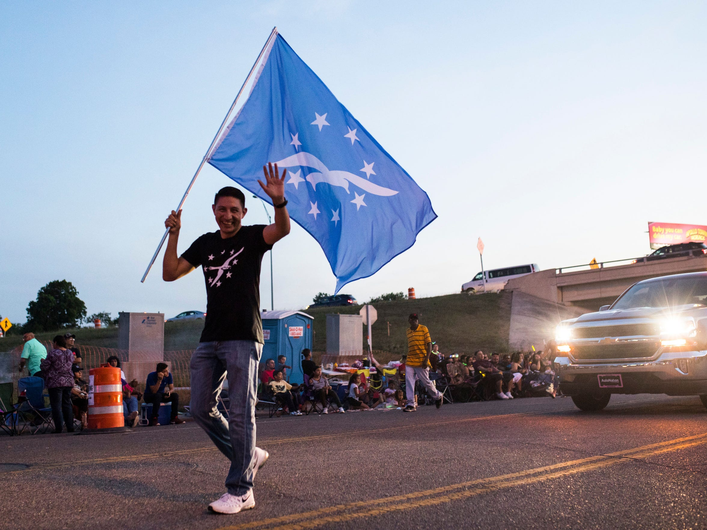 District 2 City Councilman Ben Molina waves the Corpus Christi flag while marching in the 2018 Buc Days Illuminated Night Parade on Saturday, May 5, 2018, on Leopard Street in downtown Corpus Christi.