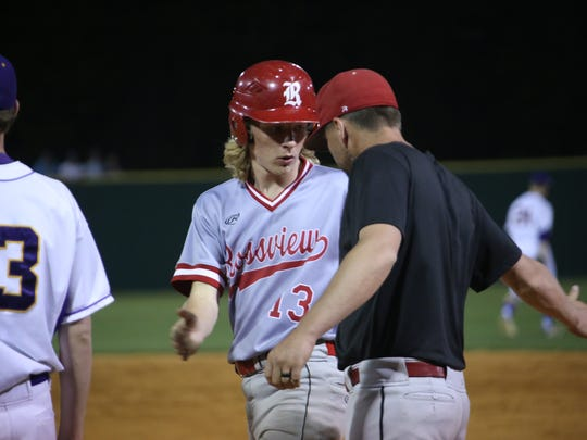 Jackson Carter (13) is congratulated by Rossview's first base coach after Jackson reached base safely late in their district tournament championship game against Clarksville High Wednesday.
