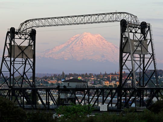 In this May 7 photo, Mount Rainier is seen at dusk and framed by the Murray Morgan Bridge in downtown Tacoma, Wash. The eruption of the Kilauea volcano in Hawaii has geologic experts along the West Coast warily eyeing the volcanic peaks in Washington, Oregon and California.