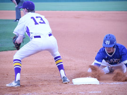 A Wilson Central batter slides back to first base to