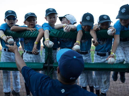 A Hooks player signs baseballs for little league players