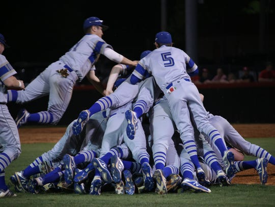 Wilson Central's team celebrate in a pile near the