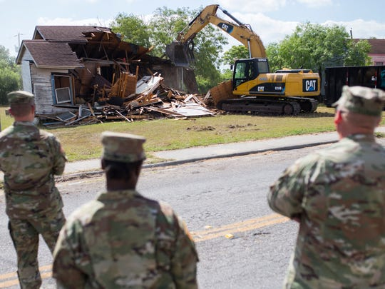 Members of the Army National Guard watch as a house is demolished in Operation Crackdown on Wednesday, May 16, 2018, on Cheyenne Street.