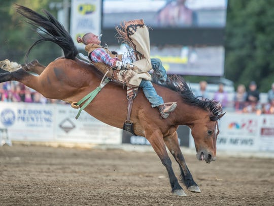 Casey Meroshnekoff of Red Bluff rides bareback in Thursday's performance of the Redding Rodeo.