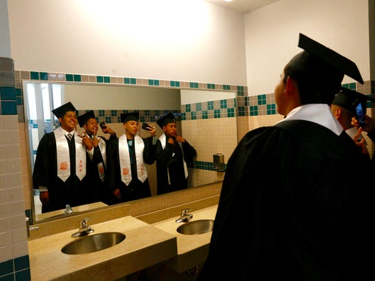 Diego Avitia, left, Konrad Bennally, Nehemiah Dee and Marquis Begaye use the restroom mirror to take photos Friday before the start of the Aztec High School graduation ceremony at Koogler Middle School in Aztec.