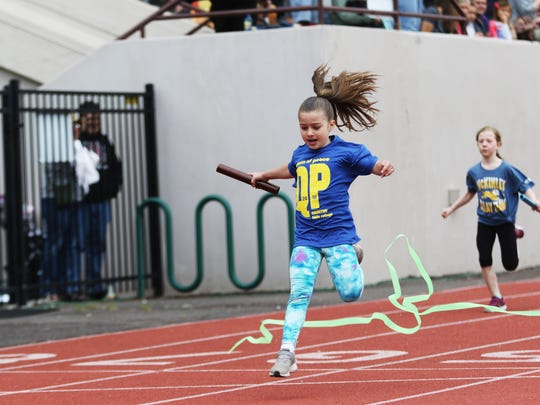 A first-grader crosses the finish line at the 44th Annual COUNTRY Kids Relay at Willamette University's McCulloch Stadium on Saturday, May 19, 2018.