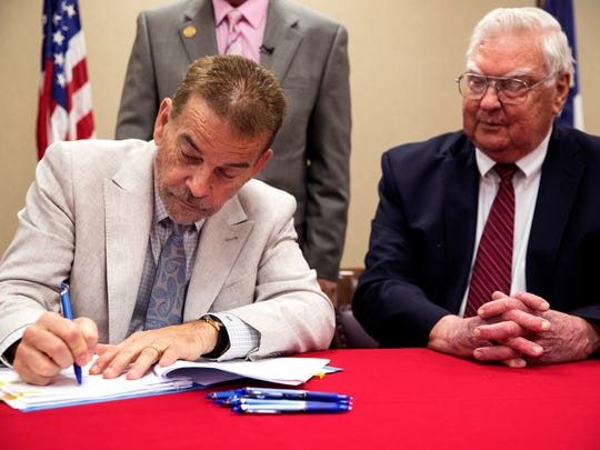 Steve Goodman (left), managing principal of Improvement Network Development Partners LLC, signs the contract purchasing the old Nueces County Courthouse just after County Judge Loyd Neal signed on Thursday, May 24, 2018. The deteriorating courthouse will be turned into a hotel.