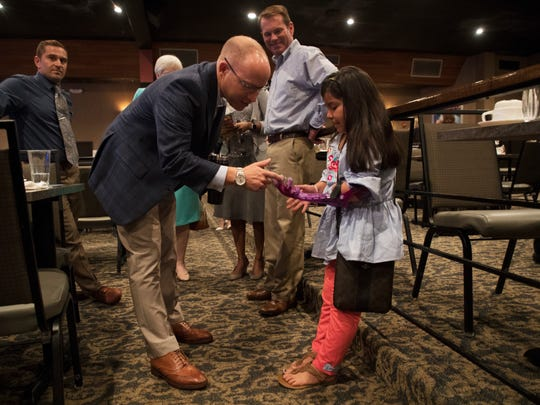 Spencer Roach checks out the Dulce Jaimes artificial limb at the 27th Annual Partners in Education – State of Our Schools Breakfast. Eric Demeri, a teacher at Sunshine Elementary School in Lehigh Acres made the limb with a 3D printer.