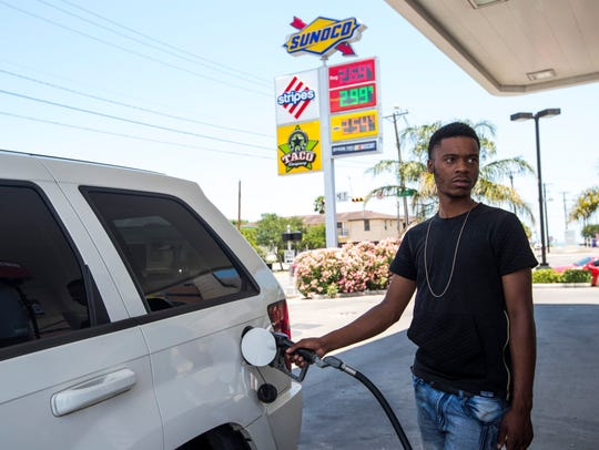 Demitrius Givines pumps gas at a Sunoco gas station