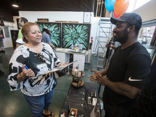 """Bertha Martinez of Moreno Valley hands ex-NFL player Ricky Williams a magazine and photo for him to sign at Atomic Budz in Cathedral City Saturday, May 26, 2018. Williams was at the Cathedral City marijuana dispensary to promote his line of cannabis health products, """"Real Wellness by Ricky Williams."""""""