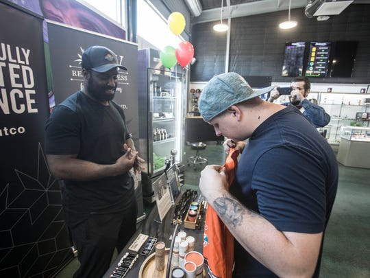 """Dylan Fenton, of Victorville, hands ex-NFL player Ricky Williams a jersey for him to sign at Atomic Budz in Cathedral City Saturday, May 26, 2018. Williams was at the Cathedral City marijuana dispensary to promote his line of cannabis health products, """"Real Wellness by Ricky Williams."""""""