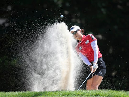 Minjee Lee, of Australia, hits from the sand onto the
