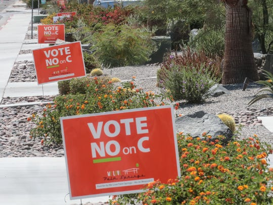 Lawn signs against Measure C posted in front of houses