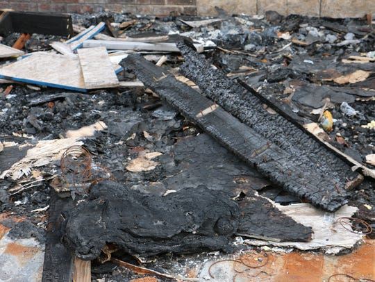 Charred boards and other debris still litter the ground