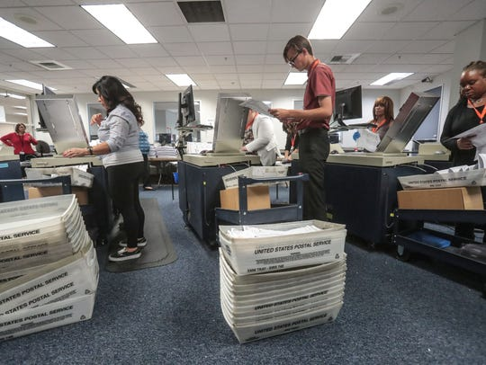 Election workers feed mail-in-ballots into machines