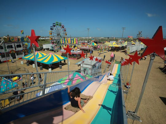 """Micah DeBenedetto/Special to the Caller-TimesKalynn Pena, 15, Adam Herrera, Caleb Martinez, 3 (from left to right) ride the """"Fun Slide"""" at the Shrimporee in Aransas Pass, Texas on June 14, 2014."""
