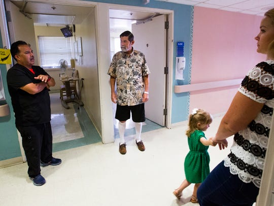 Nurse practitioner Heather Orr (left) holds her daughter Delaney Orr, 3, as Paramedic Shawn Gonzales (right) talks to Kenneth Rushing,62, at Christus Spohn hospital on Monday, June 4, 2018. Orr and Gonzales helped saved Rushing's life when he suffered a heart attack at the airport a few weeks ago.