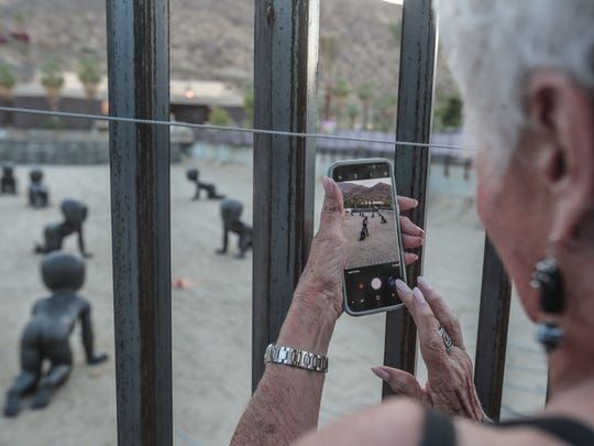 Barbara Boukather, of Palm Desert takes photos of Babies by artist David Cerny on Tuesday, June 5, 2018 in Palm Springs.