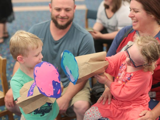 Isabella Miller, 4, and James Simons, 5, play with their Bella da Ball puppets as their guardians Amy Strunk and Aaron Strunk from Phoenix, Arizona look on during Palm Springs Library's second Drag Queen Story Hour on Wednesday, June 6, 2018.