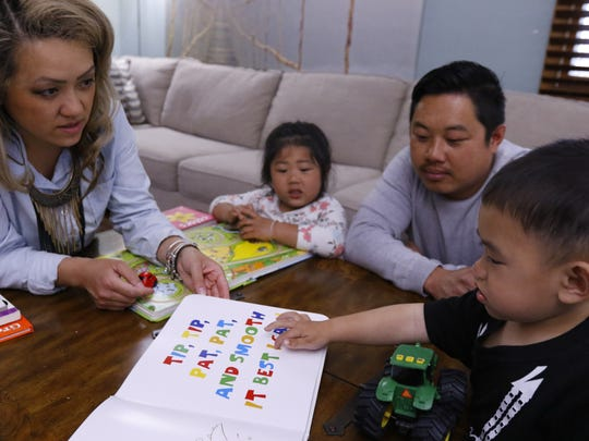Lada Xiong-Vang, left, reads to her 2-year-old son Jacobi while her 4-year-old daughter Zendaya and husband Pao look on Monday, May 21, 2018, at their house in Wausau, Wisc.