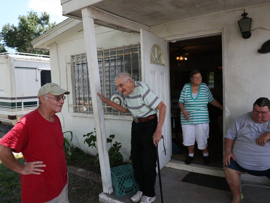 Long-time Fort Myers residents, Ralph,  92, and Jackie Hauser,88, outside of their home on Thursday. Code enforcement has cited them for having a blue tarp on their roof. They live with their son, Frank, right, on a limited income and can't get it fixed.  Area businesses rallied around the Hausers. They are getting a new roof, AC and other amenities.