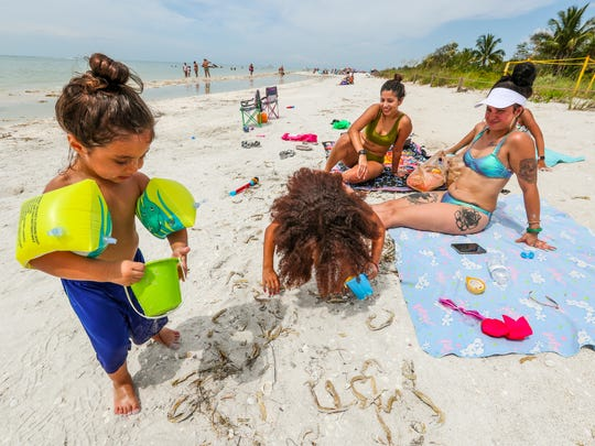 Kailani Smiley, 6, Julius Torres, 3, of Fort Myers, play in the sand near their mother. The group knew about the brown water, but came to the beach anyway. They said they will keep an eye on it. The brown water is back, and it's covering parts of Fort Myers Beach and Sanibel thanks to the Lake O releases. The fishermen and locals aren't happy about it, but on Sunday the brown water wasn't stopping beachgoers, most of them from out of town, from enjoying the water.