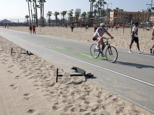 Cyclist rides by two dead Bird scooters left in the sand in Santa Monica, California. The scooters had dead batteries.