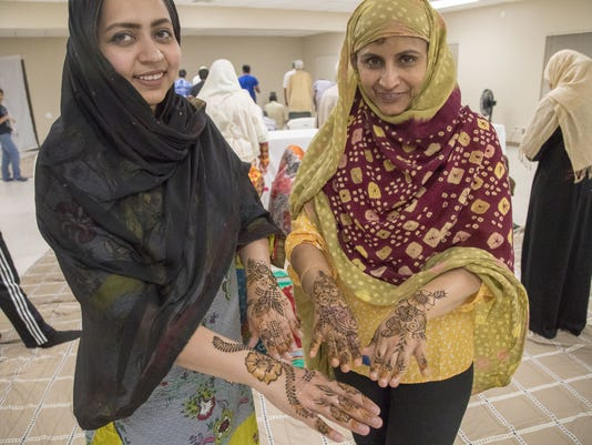 Two women show their henna