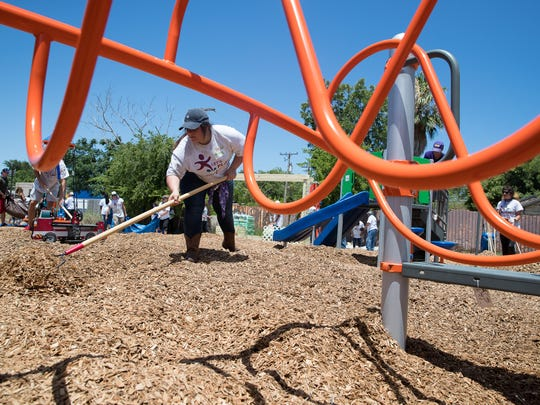 A volunteer helps KaBOOM spread mulch outside a playground the construed in a day at the Promesa College Prep-West on Thursday, June 14, 2018.