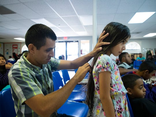 McAllen, TX, U.S.A-Manuel De Vegas Rivera, 29, brushes his daughter Linsey Victoria Rivera hair as they wait for a family member to buy them a bus ticket after being released by U.S. Immigration officials on Thursday, May 7, 2018, at the Catholic Charities Rio Grand Valley refugee center in McAllen, Texas.