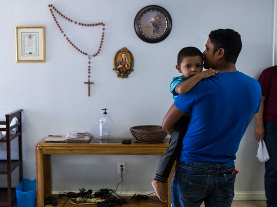 Pedro Ismael Cruz, 31, kisses his son Pedro Emanuel Cruz Chirinoz, 3, as they wait for a family member to buy them a bus ticket after being released by U.S. Immigration officials on May 7 at the Catholic Charities Rio Grande Valley refugee center in McAllen.