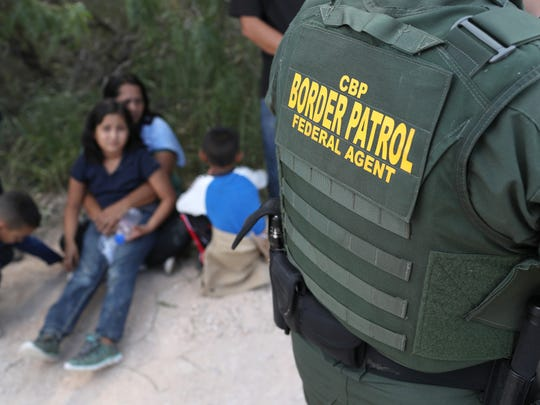 Central American asylum seekers wait as U.S. Border Patrol agents take them into custody on June 12, 2018 near McAllen, Texas. The families were then sent to a U.S. Customs and Border Protection processing center for possible separation.