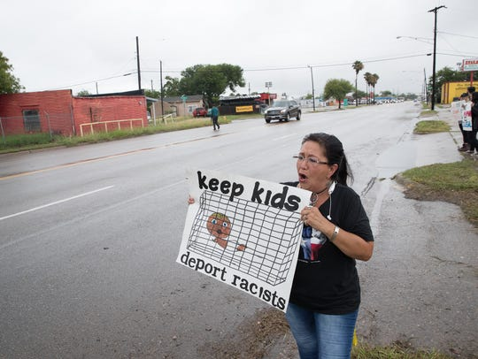 Liz Morno holds a sign calling for the end of family