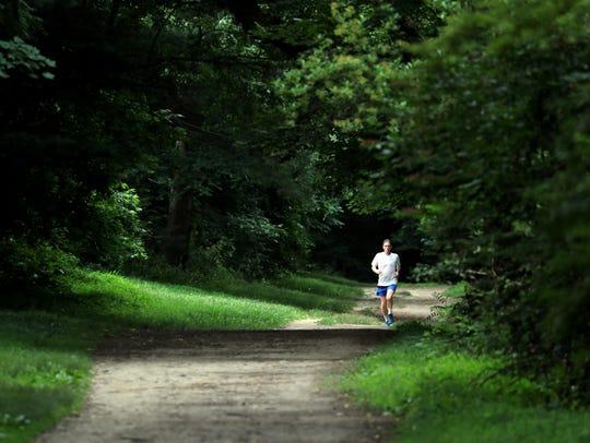 A runner runs north along the Old Croton Aqueduct trail