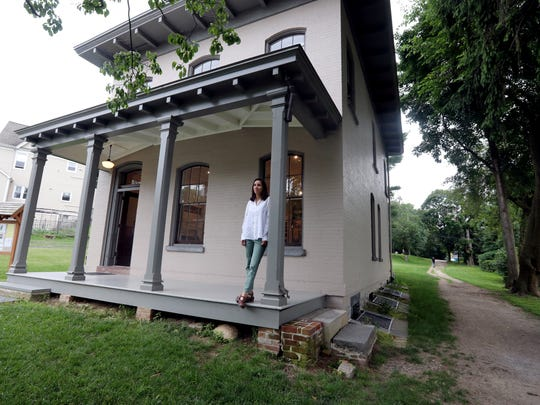 """Laura Compagni-Sabella, Interpretive Programs Organizer for the Old Croton Aqueduct Historic Park, stands on the porch of the Keeper's House in Dobbs Ferry. Last school year, Compagni-Sabella conducted a pilot program, supported by a state grant called """"Connecting Kids to Parks,"""" that taught 420 students in grades 2, 4 and 7 about water as a resource, immigrant labor, social justice, water in folktales, and plastic pollution in waterways."""