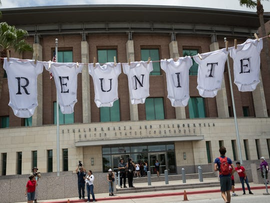 """A banner made of babe onesies reading """"Reunite"""" is"""