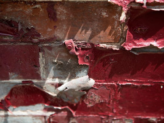 Paint peels of the brick on the side of a vacant home