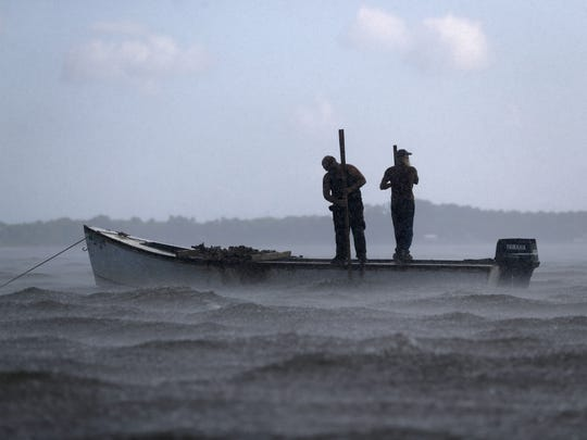 Two oystermen work through a passing rainstorm on their