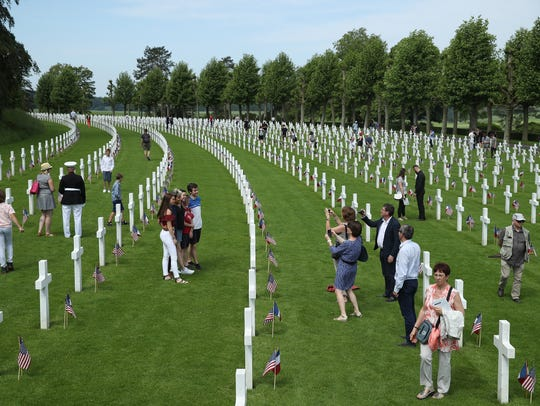 Visitors walk among the graves of U.S. soldiers, most