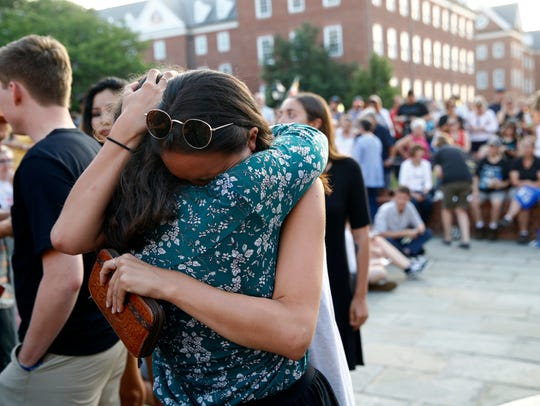 People hug as they gather for a vigil in response to