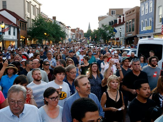 Mourners walk during a vigil in response to a shooting