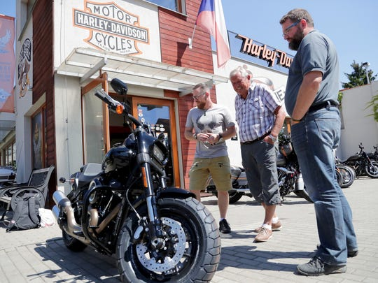 Daniel Odehnal (from left), in charge of bike sales at the Praha dealership, talks with customer Pavel Jakubec, who was renting a motorcycle, as his friend Jan Pomikácek looks on.