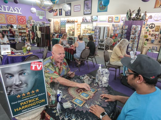 Palm Springs medium, Patrick Harrington, left, with customer Luis Colon from Arlington, Texas, at Crystal Fantasy in Palm Springs on Saturday, June 30, 2018.