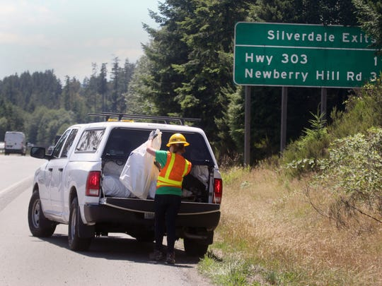 Stella Rillie, 14, from Port Orchard puts trash bags into the back of a truck that she picked up along the side of southbound Highway 3 south of Naval Base Kitsap-Bangor on Friday afternoon.