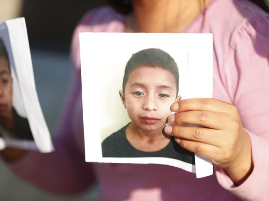 Amalia Itzep-Lopez cries as she holds pictures of her